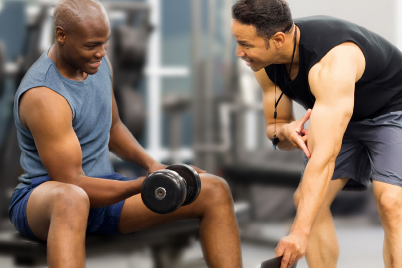 man lifting weights with trainer