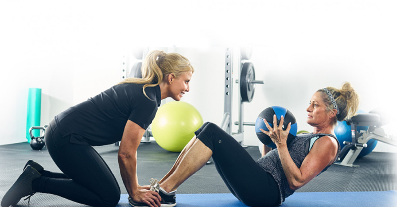 woman doing sit-ups with trainer