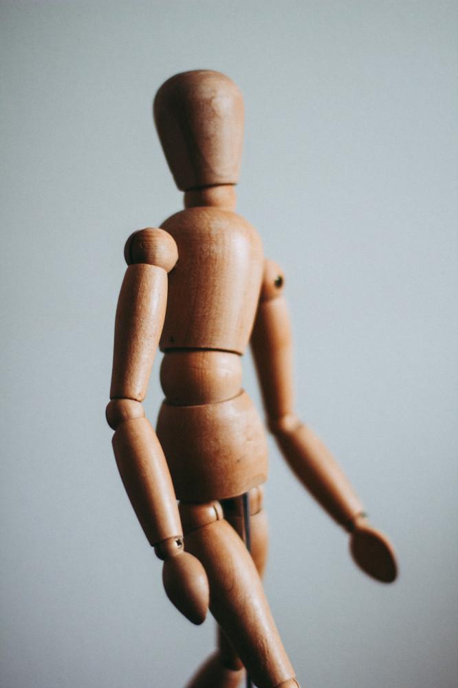 Close up photo of brown wooden doll. Photo by Kira auf der Heide on Unsplash
