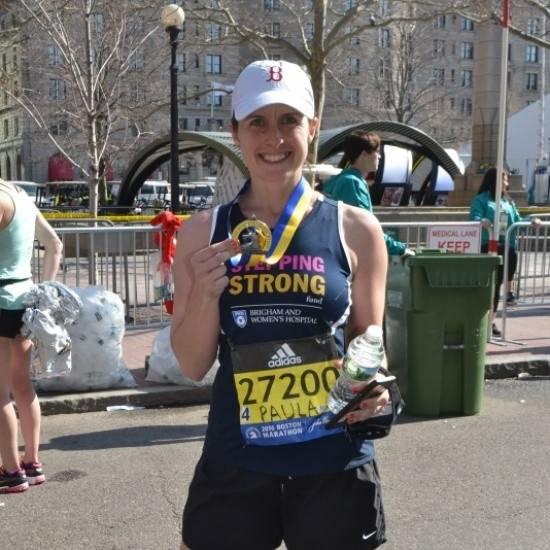 Paula holding medal after marathon run