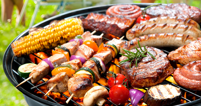 grill full of food - corn, burgers, sausage and kebabs